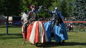 Två riddare i rustning till häst ger varandra en high five. Den ena hästen har rödvitt täcke, den andra blått.