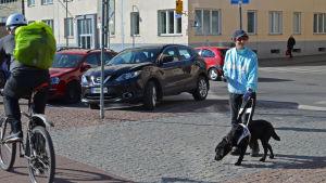Maja Lindroos med sin ledarhund väntar för att ta sig över cykelväg.