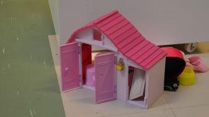 Ett rosa dockhus på ett linoleumgolv.