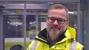 Petri Nissinen poserar i en knallgulrock framför plattform nummer ett i bussterminalen i Mattby.