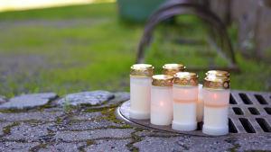 Sju gravljus står och lyser, uppställda på ett brunnslock.