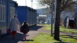 Barn och vuxen går förbi skolbarack.