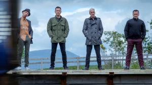 Spud (Ewen Bremner), Renton (Ewan McGregor), Simon (Jonny Lee Miller) och Begbie (Robert Carlyle) står på en perrong.