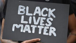 """Demonstranter höll upp skyltar med texten """"Black lives matter""""."""