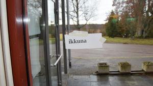 Lappar med fisnka ord finns uppklistrade på olika håll i flyktincentralen. Fönster heter ikkuna på finska.
