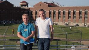Två män står framför en tegelbyggnad med en sportplan i bakgrunden och metallstaket runt.