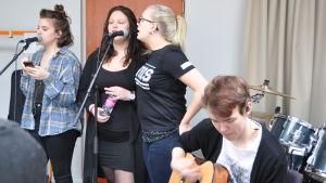 flickor från ett musikgymnasium i Tingsryd i Sverige muciserar tillsammas med en gitarrist från  Kaustby