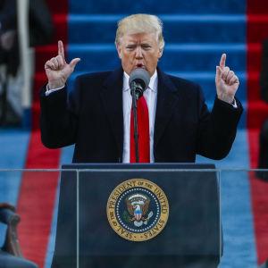 Donald Trump håller upp sina pekfingrar i luften medan han talar.