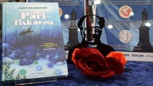 Erlandssons bok Pärlfiskaren synlig på ett bord med böcker.