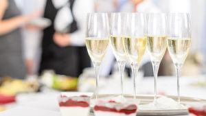 En bricka med champagne eller mousserande vin står på ett bord. I bakgrunden synd flera personer i festkläder.
