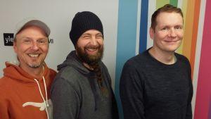 Juha-Pekka Sillanpää, Tero Vesterinen ja Jami Liukkonen seisovat Radio Suomen tunnuksen edessä.