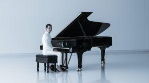 I ett helt vitt rum sitter en vitklädd David (Michael Fassbender) vid en svart flygel.