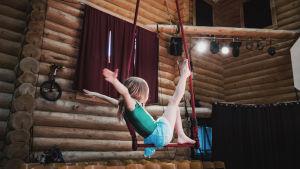 Tyttö istuu trapetsilla, kädet irti, jalka ylhäällä