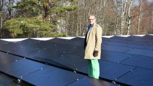 Denis Strandell står på ett tak fyllt med solpaneler.