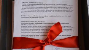 Rött silkesband runt hög med papper.
