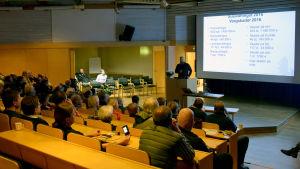 Människor sitter i ett auditorium och lyssnar på en man som håller föredrag om skador orsakade av varg.