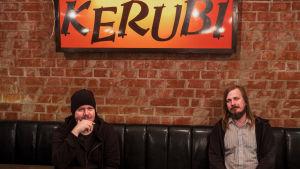 Musikerna Aki Tykki och Ville Karttunen sitter i svart lädersoffa, ovanför dem neonskylt med texten Ravintola Kerubi.