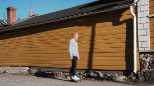 Mies skeittilaudalla, taustalla vaaleanruskea vaakalaudoitettu puutalon seinä.