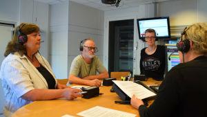 Sylva Heerman, Frank Holmlund och Kirsi Ala-Jaakkola står i Yle Västnylands radiostudio. Till höger syns programledaren Marica Hildén.