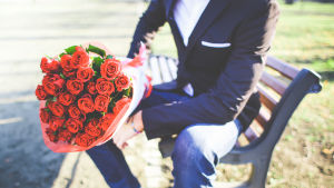 Man med röda rosor på en bänk.