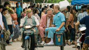 Allan (Robert Gustafsson) kör en moped genom en folkmängd, i sidovagnen sitter Julius och Gäddan.