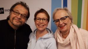 Kalevi Pollari, Monna Kamu ja Iris Mattila seisovat Radio Suomen tunnuksen edessä