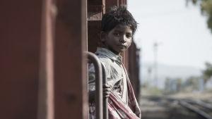Saroo (Sunny Pawar) står på trappsteget till ett tåg och ser rakt in i kameran.