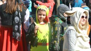 En pojke utklädd till drake.