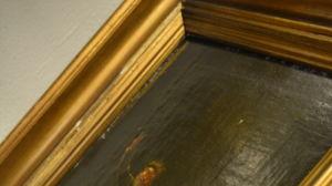 närbild av en oljemålning i guldram