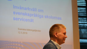 """Man i profil framför texten """"Invånarkväll om svenskspråkiga skolornas servicenät""""."""