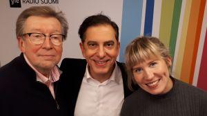 Olli Ahvenlahti, André Chaker ja Anna Keränen seisovat Radio Suomen tunnuksen edessä