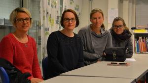 Fyra kvinnor sitter bakom bord i ett klassrum.
