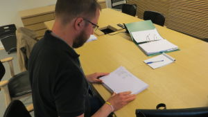 Redaktör Linus Lång går igenom utskrifter av riksdagens besökarlistor.