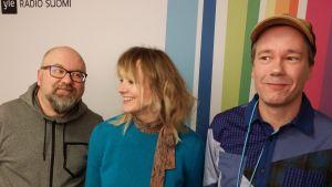 Juha Blomberg, Jonna Tervomaa ja Jussi Jaakonaho seisovat Radio Suomen tunnuksen edessä