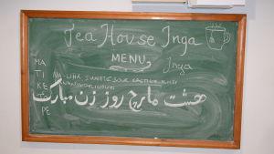 tavla med text på finska, engelska och arabiska