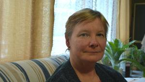 Profilbild på Outi Haanpää som sitter i en soffa.