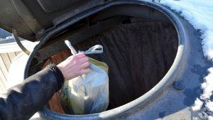Skräppåse lägs i avfallskärl