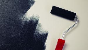 Ett målarverktyg med rött handtag och svart färg.