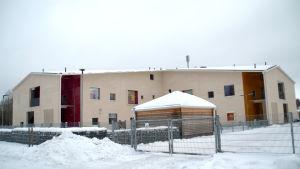 En beige, rätt så nybyggd byggnad. Huset är omgärdat med ett stängsel och marken är täckt av snö.