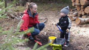 Jennie Lipasti med sonen Väinö leker med spadar och plastskottkärra