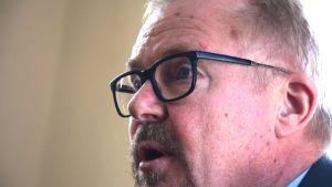 En ansiktsbild av Raseborgs stadsdirektör Ragnar Lundqvist, lite i profil från vänster. En man i övre medelåldern med svartbågade glasögon.