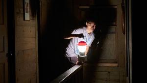 Travis (Kelvin Harrison Jr.) med lykta i handen smyger fram i en mörk korridor.