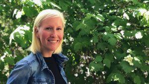 Marknadsföringschef på Sets Hedda Sirén ler framför en buske.