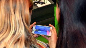 Två flickor ser på ett spel på sin telefon.