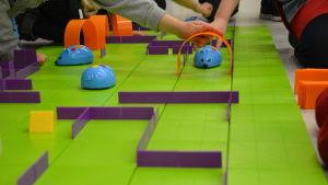 Flera barn jobbar med en robotmus som ska klara en labyrint.