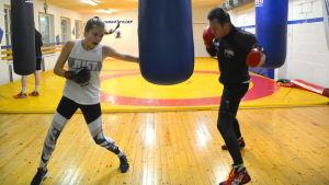 Aslak och Vera sparrar mot en boxningssäck.