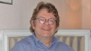 Robert Harling sitter i soffan, skrattar  och ser glad ut.