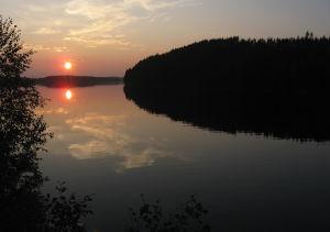 Aurinko laskee järvimaisemassa.