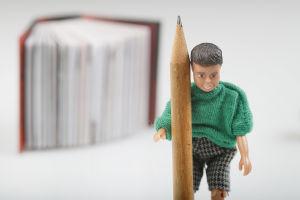 En docka som håller i en penna, framför en bok.