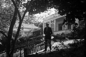 Mies seisoo portailla puutarhassa.